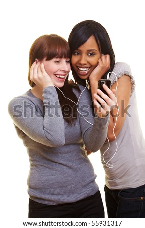 Two happy young women listening to music with a cell phone