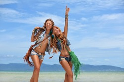 two happy young women on the beach