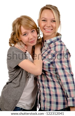 Two happy young women relaxing together standing with their arms around each others necks smiling at the camera, studio portrait isolated on white - stock photo