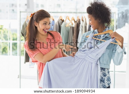 Two happy young women shopping in clothes store