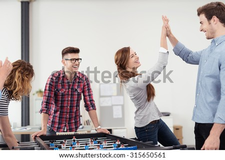 Two Happy Young Workmates Showing High Five After Winning a Table Soccer Game Inside the Office.