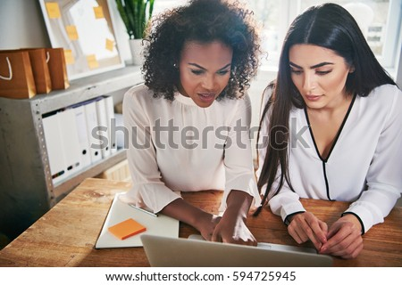 Two hardworking young female entrepreneurs working together on a laptop computer reading the screen with serious engrossed expressions, high angle view