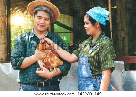 Two hasband and wife, Asian farmers are carrying a hen Which they fed on the farm, to chicken farm concept. #1452601145