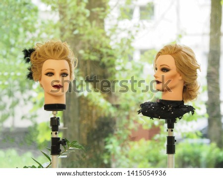 Two heads of mannequins with hairstyles. European hairstyle on the head of a mannequin on a light background. #1415054936