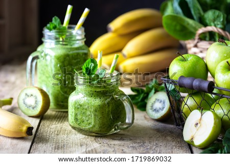 Two healthy green smoothies with spinach, banana, apple, kiwi and mint in glass jar and ingredients. Detox, diet, healthy, vegetarian food concept