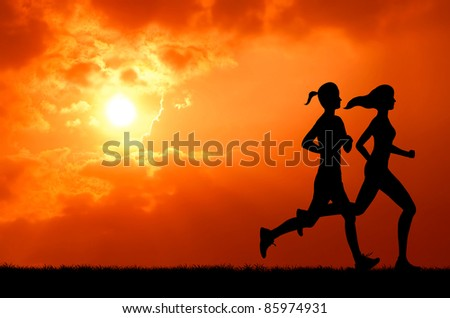 two healthy young woman run together at sunset silhouetted