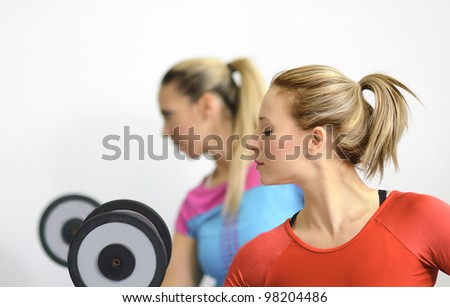 Two healthy young women on light background working out in the gym lifting dumbbells.