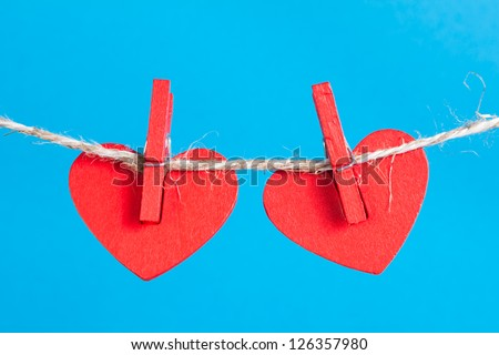Two heart on clothesline with clothespins, blue background