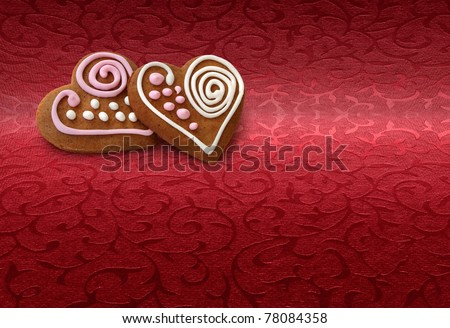 Two heart shape cookies on Christmas red brocade fabric