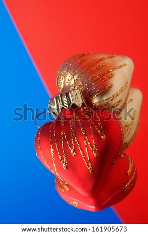 Two heart shaped christmas ornaments on blue red background