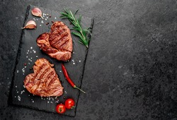 Two heart shaped grilled marble beef steaks with spices on a stone background