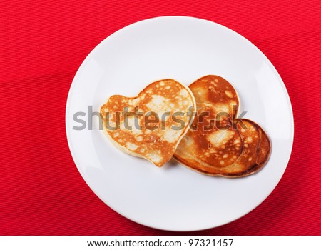 Two heart-shaped pancakes on a plate - stock photo
