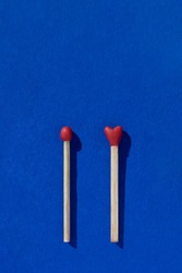 Two heart shaped red matchsticks couple, blue background. Сoncept of perfect match, fire of love and passion. The one and only. Happy Valentines Day. Holiday romantic wedding poster, greeting card.