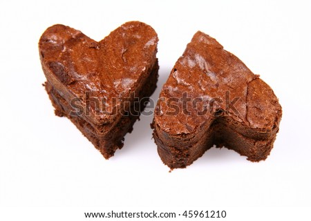 Two heart shaped slices of a brownie on white background