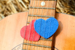 Two heart symbols, red and blue colored, is placed together under guitar strings. Romantic feelings and musical creativity. Concept of love song and music for people in love