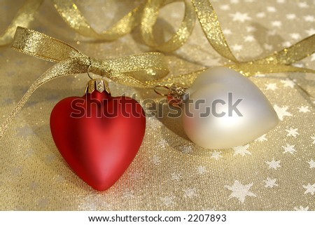 Two Hearts and sparkling gold ribbon on a sparkling star background. - stock photo