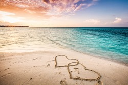 Two hearts drawn on a sandy beach by the sea. Sunset view. Love symbol.