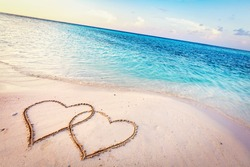 Two hearts drawn on sand of a tropical beach at sunset. Clear turquoise ocean. Maldives islands.