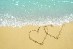 Two hearts drawn on the sand beach being wash away by a wave representing divorce, breakup concept.