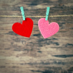 two  hearts hanging on a cord on a wooden background, love background