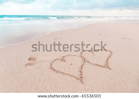 Two hearts in the sand with footprints leading into the ocean