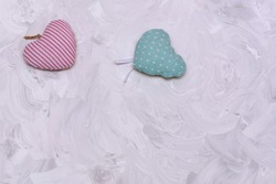 Two hearts made of fabric, pink and blue on gray textured background. Copy space for text. Concept for Valentine's day, lovers, wedding.