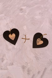 Two hearts made of graphite and wood on gray textured background. Heart plus heart together. Concept for Valentine's day, lovers, wedding.