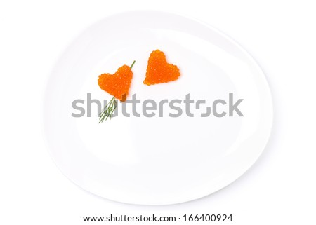 two hearts of red caviar with dill on a plate, isolated on white