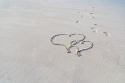 Two hearts on the beach, tropical honeymoon or anniversary.  Drawing in sand with footsteps. Romantic travel concept