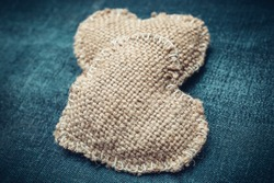 Two hearts on the jeans texture. Toned image.