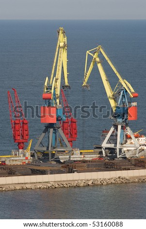 Two heavy industrial cranes working at the commercial dock in the middle of a day