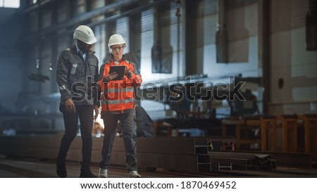 Two Heavy Industry Engineers Walk in Steel Factory, Use Tablet and Discuss Work. Industrial Worker Uses Angle Grinder in the Background. Black African American Specialist Talks to Female Technician.