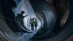 Two Heavy Industry Engineers Walking Inside Pipe, Use Laptop, Have Discussion, Checking Welding. Construction of the Oil, Natural Gas and fuels Transport Pipeline. Industrial Manufacturing Factory