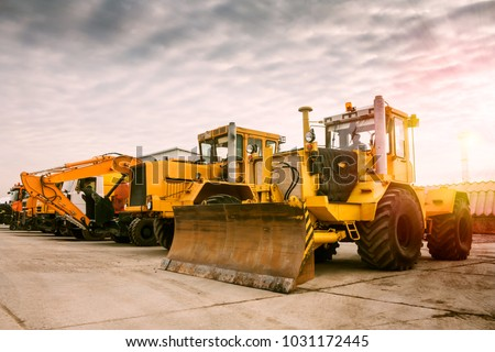 Two heavy wheeled tractor one excavator and other construction machinery in the morning sun