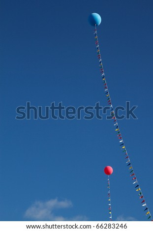 Two  helium balloons, one red and one blue, held in place by a flagged line against a blue sky