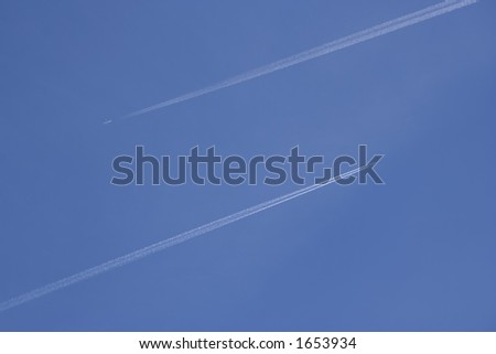 Two high-flying aircraft flying in opposite directions with contrails