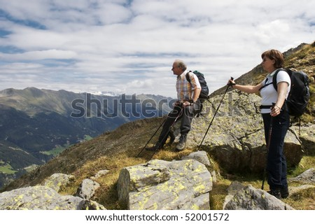 Two hiker resting near mountain summit of Lepples Kofel and being amazed about stunning view of the Alps mountain range and beautiful Defereggen valley in summer, Tyrol, Austria.