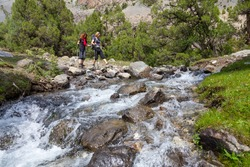 Two hikers crossing fast flowing river. People going across mountain creek with fast streaming water jumping on the rocks green meadow and forest along river