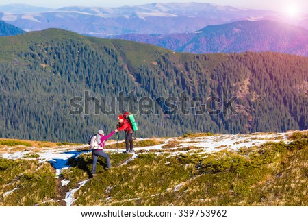 Two Hikers in Mountain Landscape Man helping Woman to climb on steep Ridge Forest Hills and shining Sun on Background