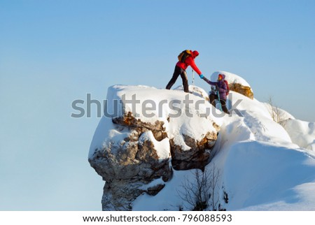 two hikers on top of the mountain in winter; a man helps a woman to climb a sheer stone #796088593