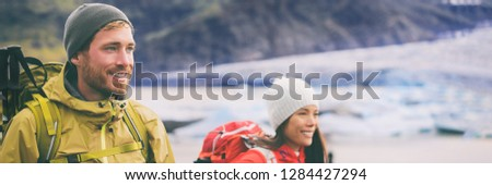 Two hikers people walking together hiking in wilderness. Alpine climbers mountaineering couple trekking in ice snow mountains. Panorama banner of team hiking in winter.