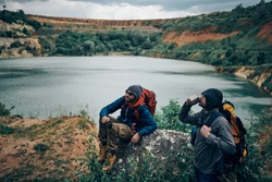 Two hikers taking a break in the nature and drinking coffee.