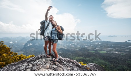 Two hikers taking selfie from top of the mountain with valley view on the background