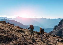 Two Hikers with Backpacks and walking Sticks walking on grassy Trail towards rising Sun. Layered Mountains View and clean Sky on sunny Background