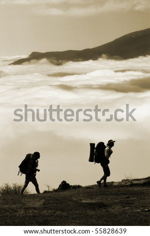 Two hikers with backpacks climbing a peak on cloud sky background