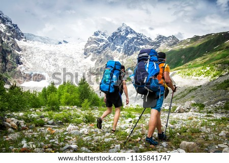 Two hikers with large backpacks in mountains. Tourists hike on rocky mounts. Leisure activity on mountain trek. Adventure of men in wild Svaneti region of Georgia. Groupe Hiking #1135841747