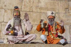 Two hindu sadhu holy man, sits on the ghat, seeks alms on the street in Jaisalmer, Rajasthan, India. Close up