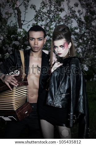 Two hippie punks - fashion girl and boy in black clothes with accordion. Hippie style