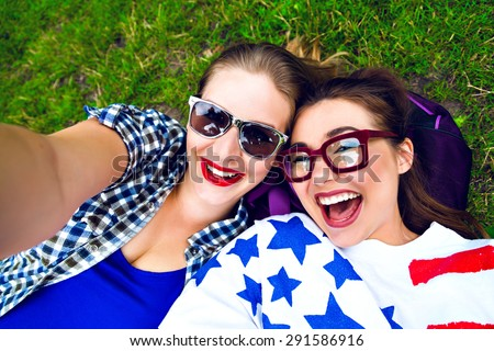 Two hipster girls having fun and making selfie in the park, smiling and screaming, wearing sunglasses and bright clothes, best friends relax end enjoy weekend.