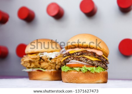 Two homemade delicious burger on colorful background. Front beef burger in focus loaded with double patty, cheese, lettuce, onion, tomato, second is blurred with crispy chicken and coleslaw. - Image Stock photo ©